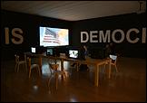 Oliver Ressler. What Is Democracy?, 2009. Video-instalación de 8 canales. Vista general en la Bienal de Lyon 2009. Cortesía del artista