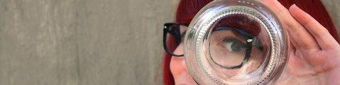 Mujer mirando a través del cristal de una botella