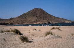 Imagen próxima de un cono volcánico en Cabo de Gata, en primer término dunas litorales actuales
