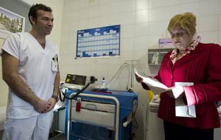 Una paciente lee su factura informativa ante un profesional sanitario. (Foto EFE)