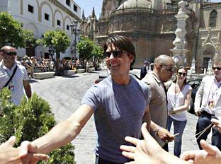 El actor Tom Cruise saluda a un grupo de admiradores en Sevilla.