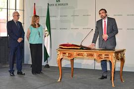 La presidenta y el consejero de Economía observan el momento en que el rector de la Universidad de Jaén toma posesión de su cargo.