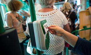 Una usuaria del Metropolitano de Granada valida su billete al subir al tren.