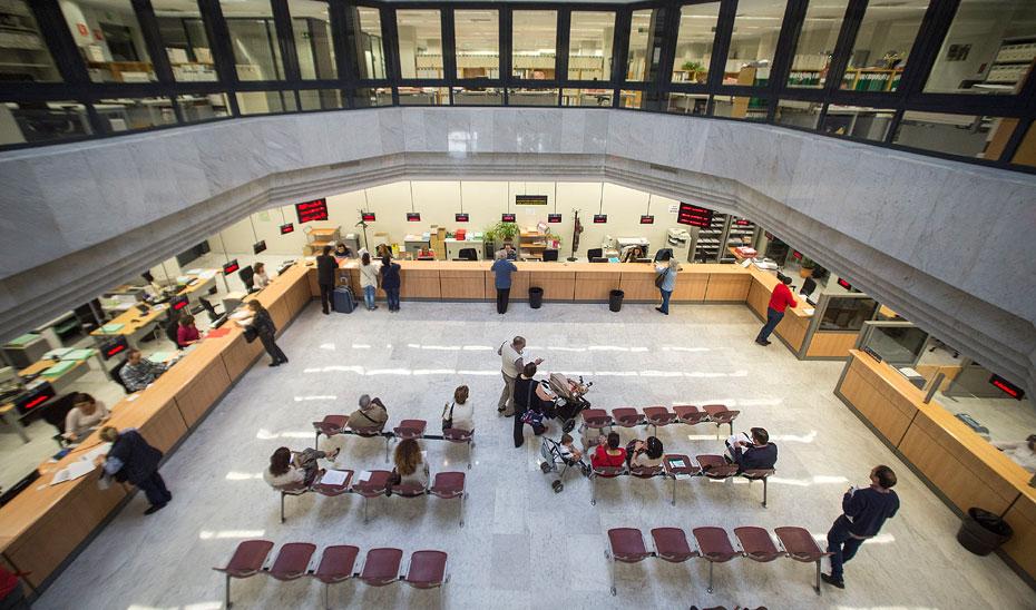 Funcionarios atienden a varios ciudadanos en un edificio administrativo.