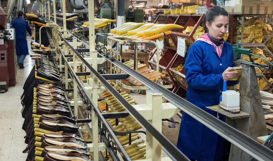 Una mujer trabajando en una fábrica de calzado.