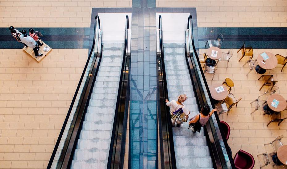 Clientes de un centro comercial bajando por las escaleras mecánicas a la planta de moda y restauración.
