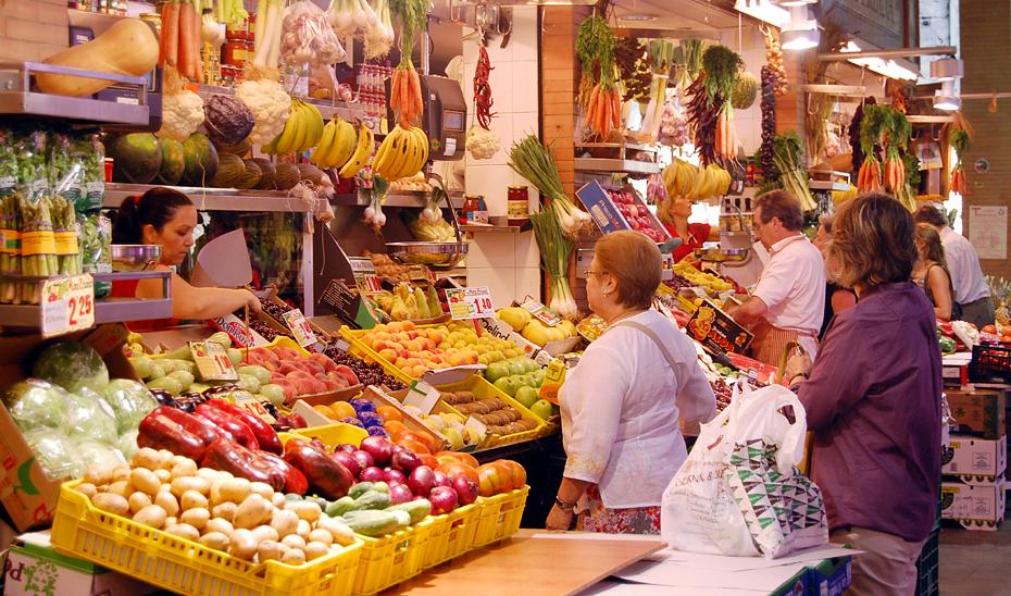 Consumidores comprando en un mercado de abastos.