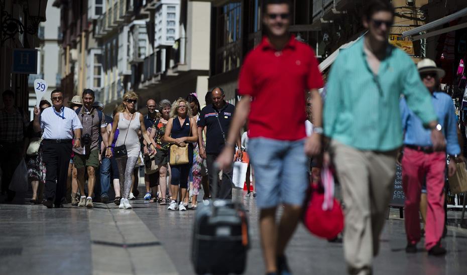 Un grupo de turistas camina por detrás de su guía.