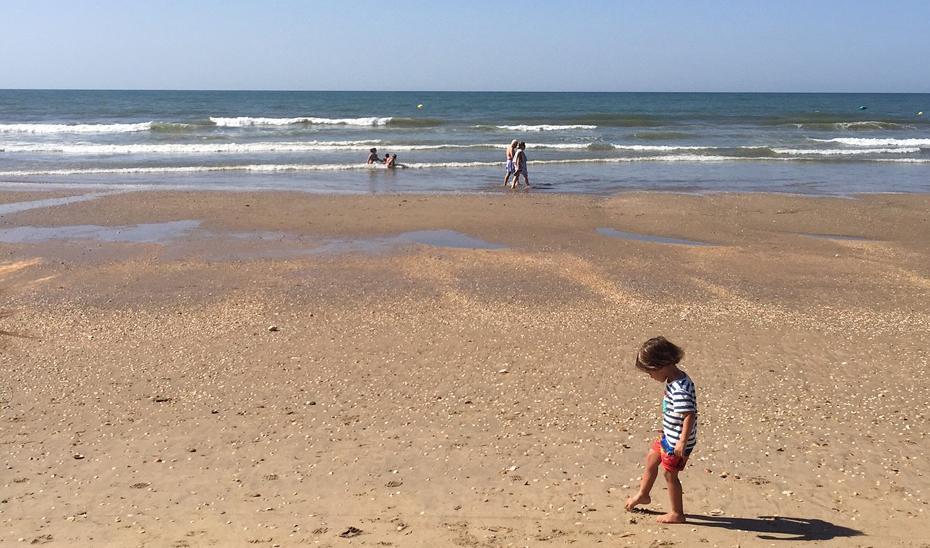 Un niño juega en la arena de una playa andaluza con paseantes y bañistas al fondo.