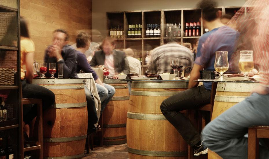 Clientes disfrutando de unas copas de vino en un bar.