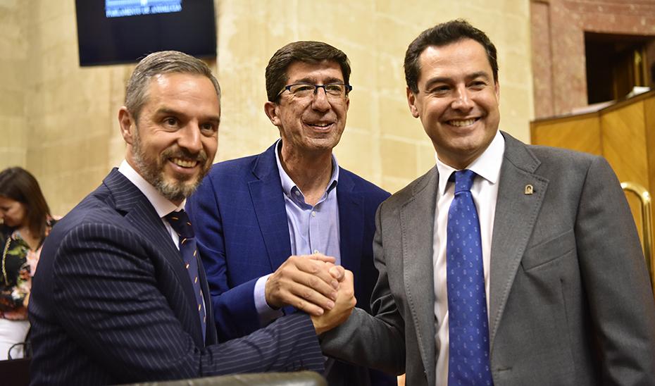 Juanma Moreno, Juan Marín y Juan Bravo se felicitan después del debate de totalidad del Presupuesto, en el Parlamento.