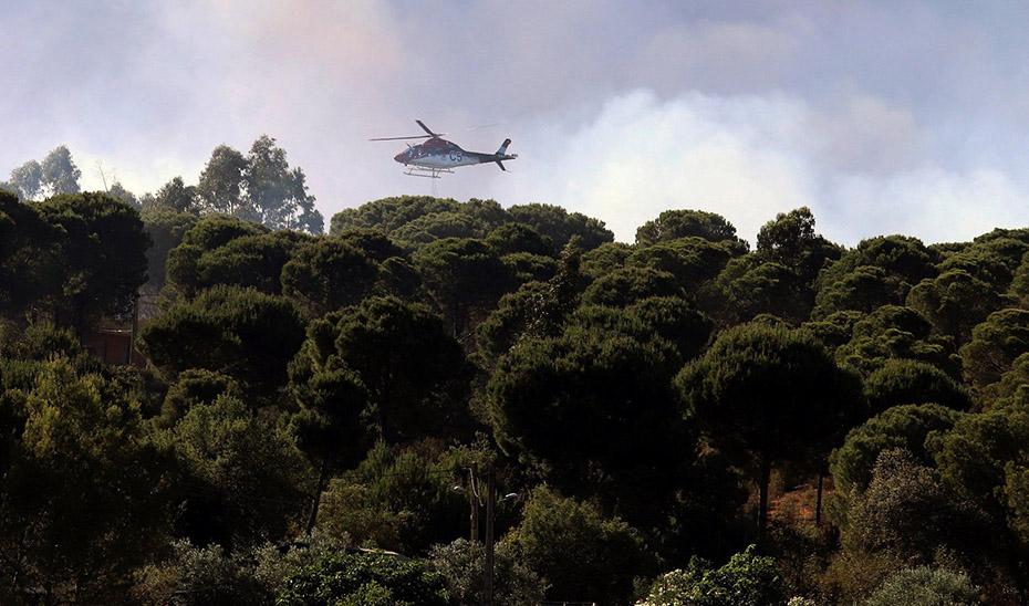 Un helicóptero contraincendios trata de sofocar un fuego declarado en un espacio forestal.