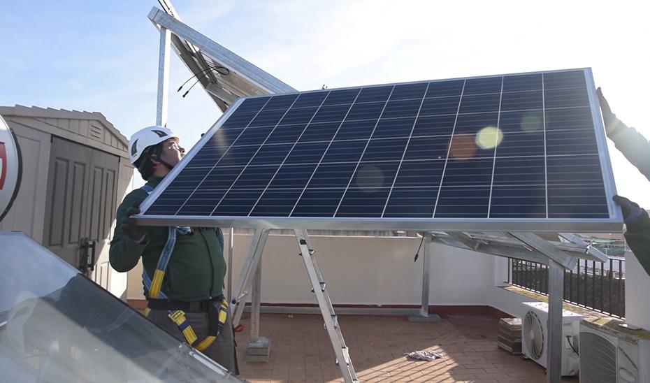 Operarios instalan placas solares para autoconsumo doméstico.