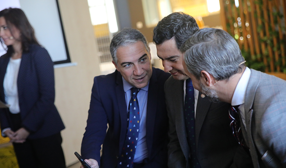 El presidente Juanma Moreno comprueba, con Elías Bendodo y Juan Bravo, el funcionamiento de la app.