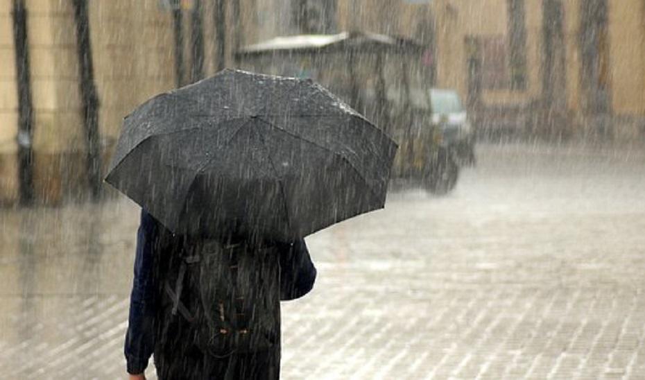 Una persona camina bajo la lluvia.