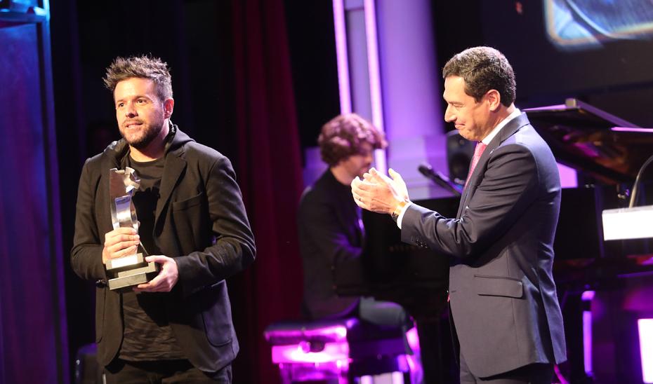 El presidente Juanma Moreno, tras entregar el premio a Pablo López.