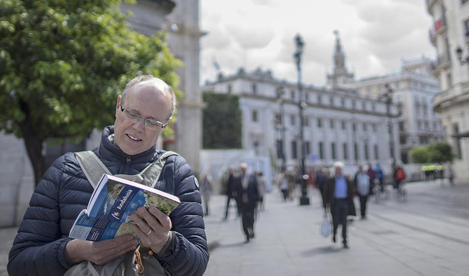 Un turista consulta una guía de Andalucía en Sevilla.