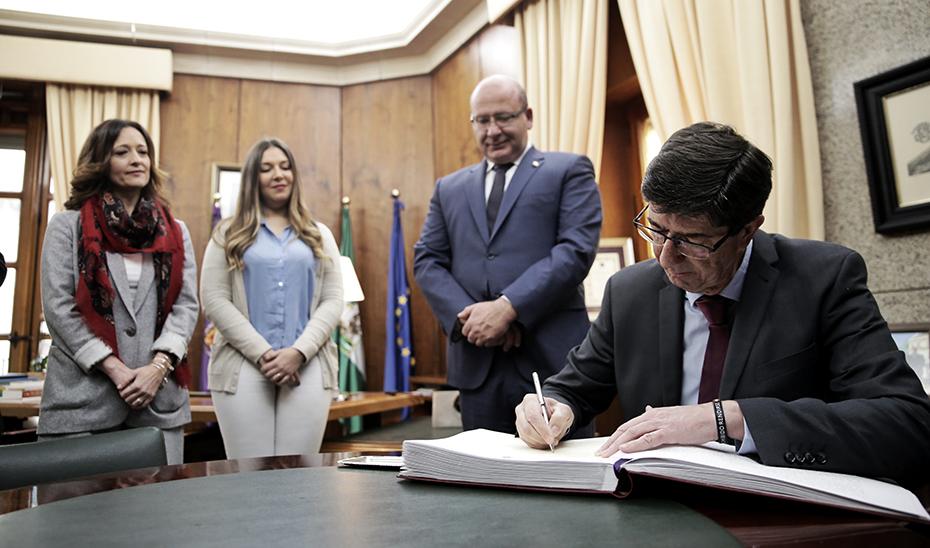 Juan Marín firma en el Libro de Honor del Ayuntamiento de Jaén, en presencia del alcalde.