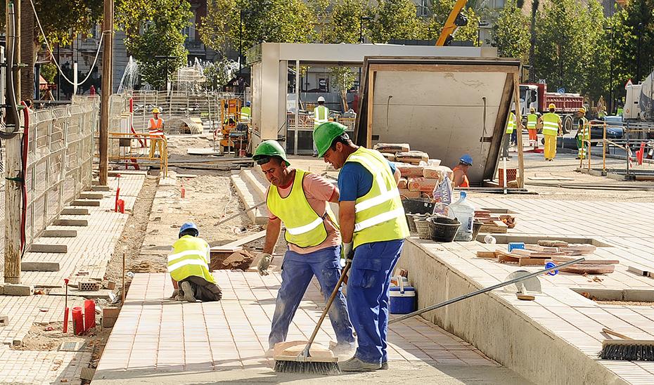Albañiles trabajando en la construcción de una rampa en una zona peatonalizada.