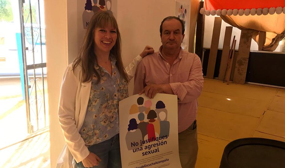 La asesora de programa del IAM en Córdoba, Lourdes Arroyo, mostrando con un técnico uno de los carteles repartidos por la Feria.