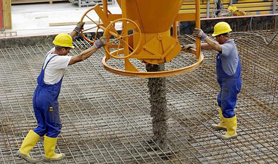 Obreros de la construcción completando un proceso de cimentación.