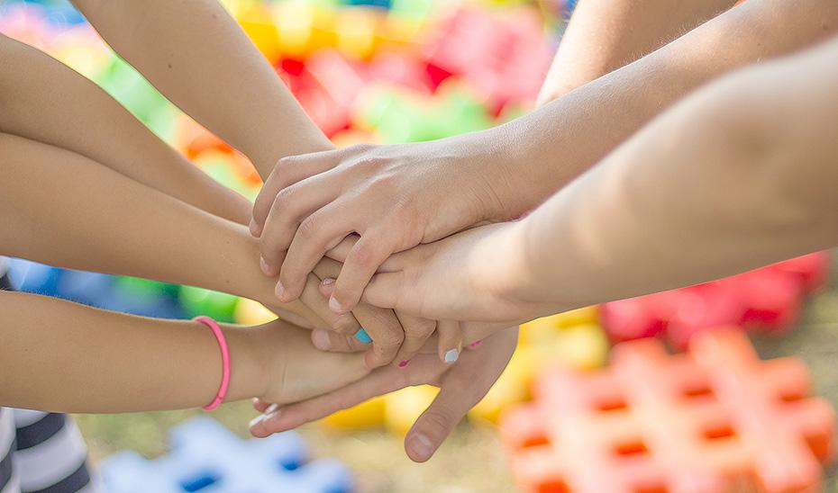 Varios niños unen sus manos como muestra de una buena convivencia.