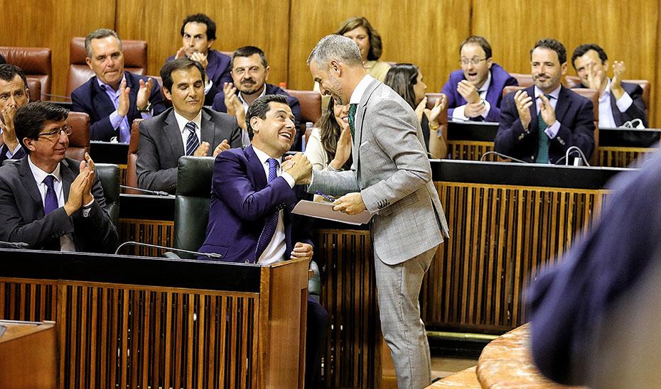 El presidente de la Junta, Juanma Moreno, y el vicepresidente, Juan Marín, felicitan al consejero de Hacienda, Juan Bravo, por su defensa de las cuentas para 2019.