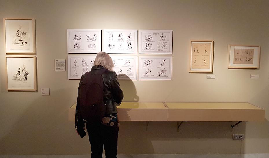 Una mujer observa algunos de los dibujos expuestos de Martínez de León.