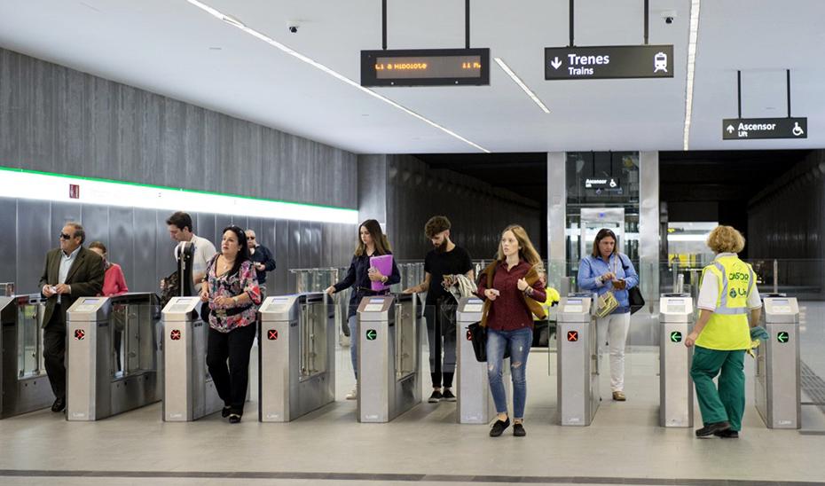 Usuarios del metro de Granada pasando por los tornos de control de acceso.