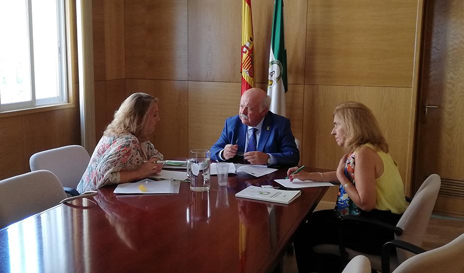 El consejero de Salud y Familias, Jesús Aguirre, junto a la delegada en Córdoba, escucha a May Escobar, directora de la Fundación Luzón.