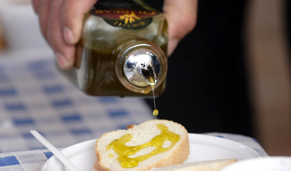 Cliente de un negocio hostelero sirviéndose aceite en pan.