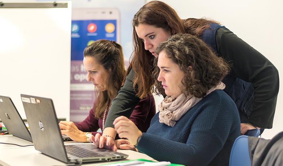 Alumnas de un curso de capacitación digital reciben indicaciones de su monitora.