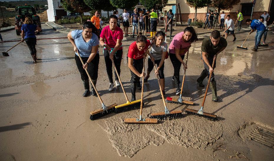 Un grupo de personas recogen el barro tras el paso de la DANA.