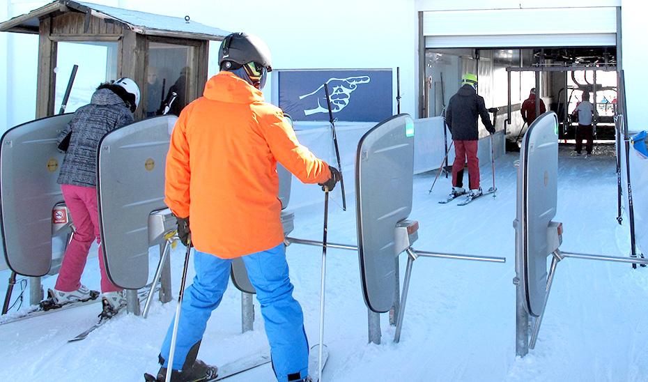 Un esquiador se acerca a los tornos de acceso a los remontes.