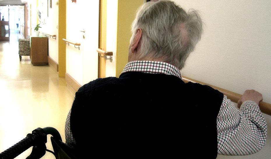 Una persona en silla de ruedas se desplaza por los pasillos de una residencia.