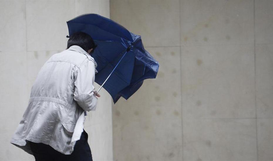 Un hombre se protege con un paraguas de la lluvia y el viento (Agencia EFE).