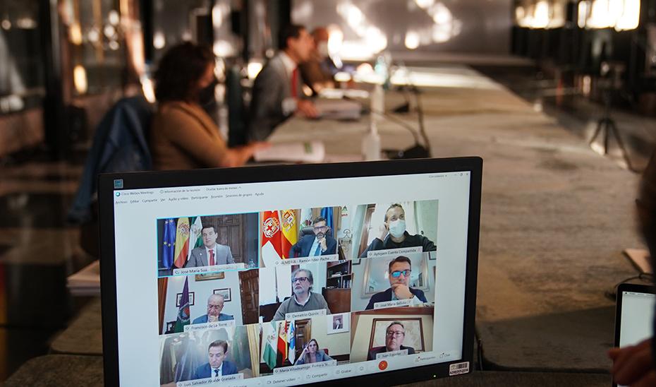 El presidente de la Junta y los alcaldes de las ocho capitales andaluzas, en un monitor durante la reuniíon.