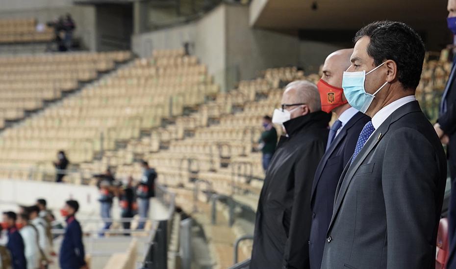 El presidente Juanma Moreno escucha con atención los himnos de España y Alemania antes del partido.