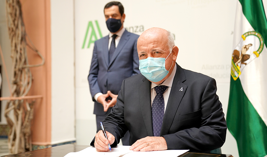 El consejero de Salud y Familias, durante la firma del convenio, en presencia del presidente Juanma Moreno.