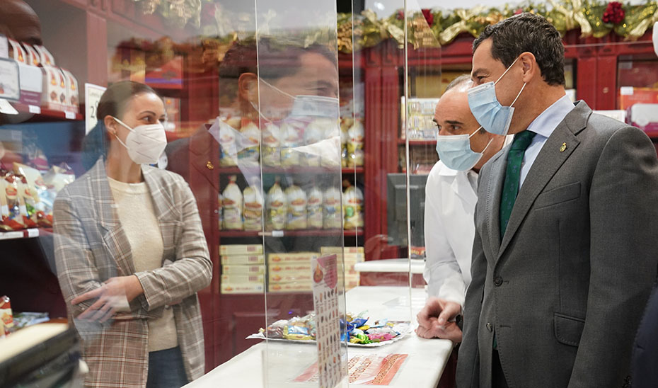 El presidente andaluz conversa con una de las trabajadoras de la fábrica de dulces La Flore de Rute.