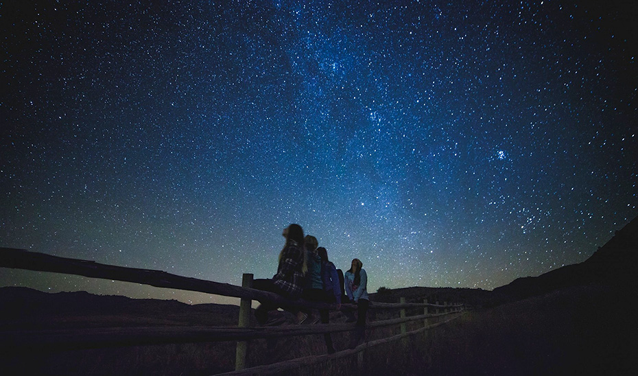 Un grupo de jóvenes observa las estrellas en un espacio sin contaminación lumínica.
