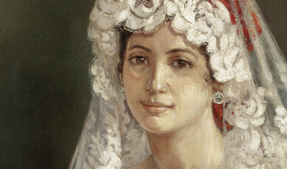 En el cabello de la modelo se observan, bajo las transparencias de la mantilla, claveles rojos.