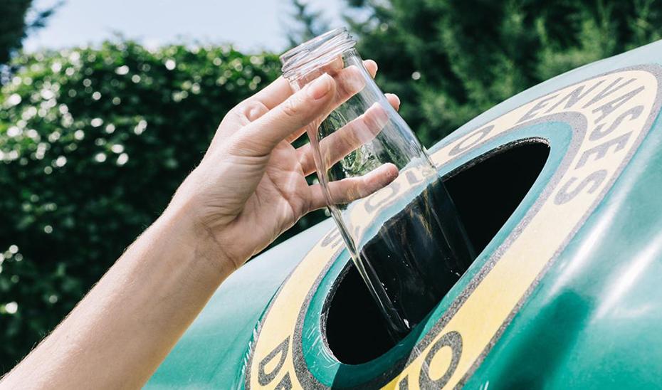 Una persona deposita una botella de vidrio en un contenedor.