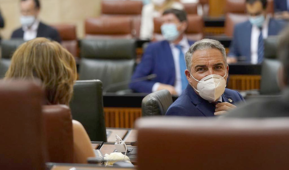 El consejero Elías Bendodo, en su escaño y con mascarillas, en los instantes previos al inicio del pleno.