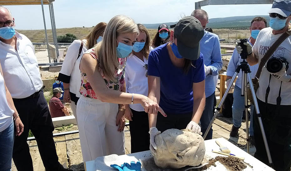 La consejera de Cultura y Patrimonio Histórico, Patricia del Pozo, observa la cabeza hallada en el Conjunto Arqueológico de Cástulo.