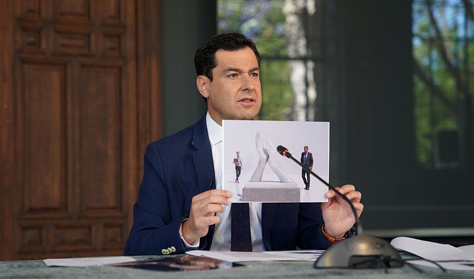 Juanma Moreno sosntiene la imagen de la propuesta de monumento a los profesionales que luchan contra el Covid-19.