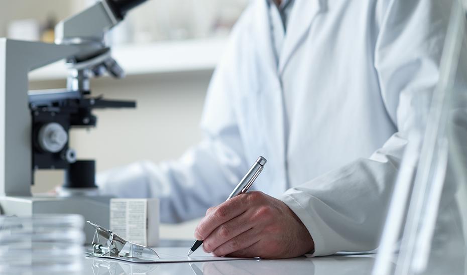 Un investigador toma notas junto a un microscopio.