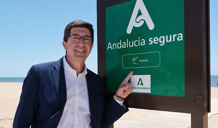 El vicepresidente de la Junta, Juan Marín, junto al cartel con el distintivo \u0027Andalucía Segura\u0027 en una playa del litoral andaluz.