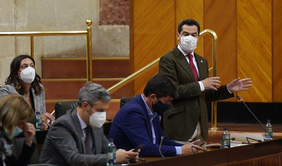 Juanma Moreno, desde su escaño, interviene ante los parlamentarios andaluces durante la sesión de control.