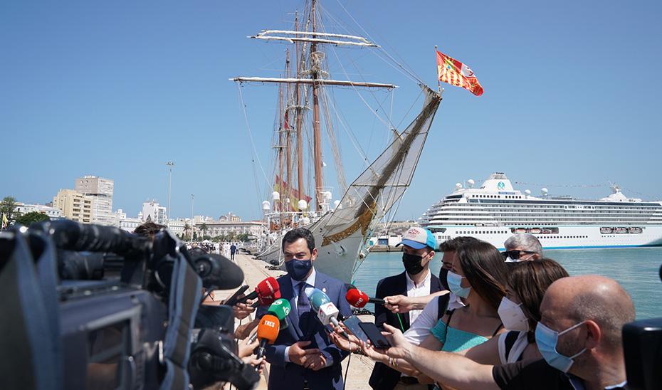 El presidente Juanma Moreno atiende a los medios ante el Juan Sebastián Elcano, atracado en el puerto de Cádiz.